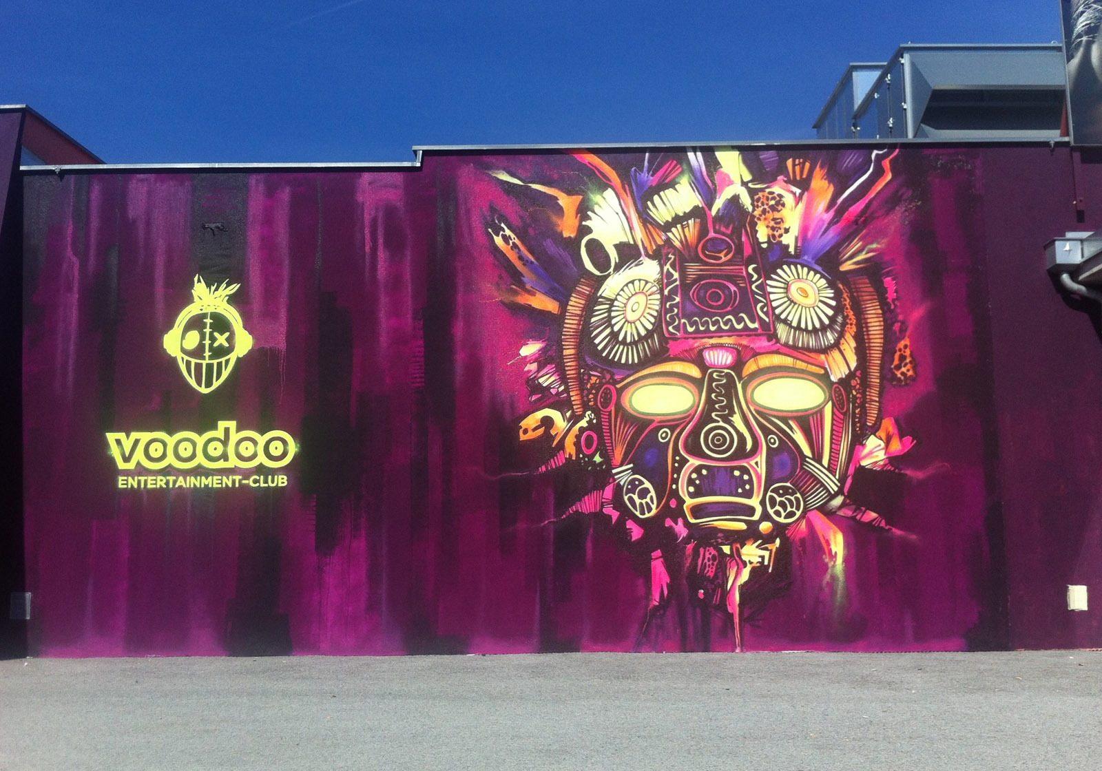 graffitiauftrag-graffitikuenstler-artmos4-voodoo-disco-fassadengestaltung-maske-neon