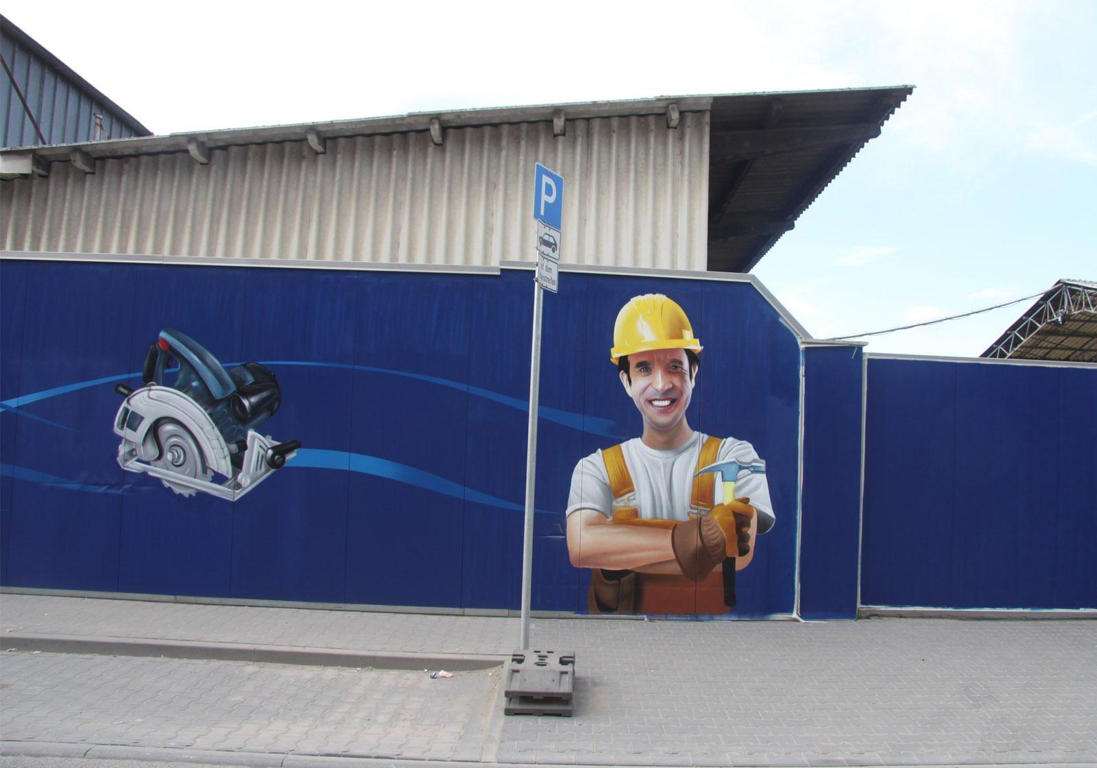 graffitikuenstler-graffitiauftrag-artmos4-rhein-main-baumaschinen-2013-bohrer-menschen-fotorealistisch-blau-orange-aussen
