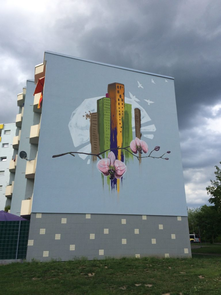 graffitiauftrag-graffitikuenstler-artmos4-Baugenossenschaft_Odenwaldring_2012_skyline_landschaft_aussen_gebäude_bunt_kunst