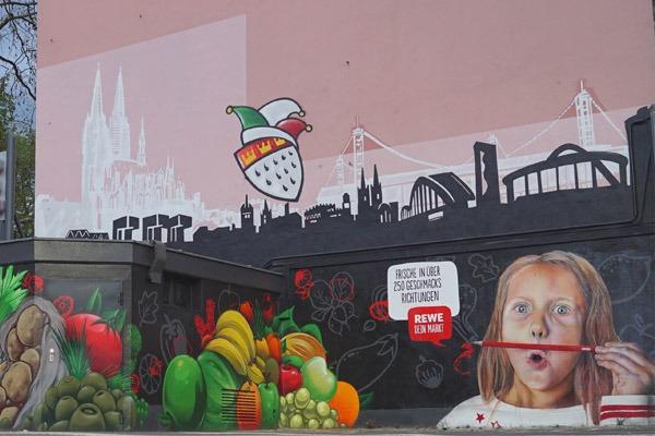 graffitiauftrag-graffitikuenstler-artmos4-rewe-2018-skyline-obst-gesicht-schrift-wappen-aussen-schwarz-bunt-fotorealistisch-illustrativ-handel