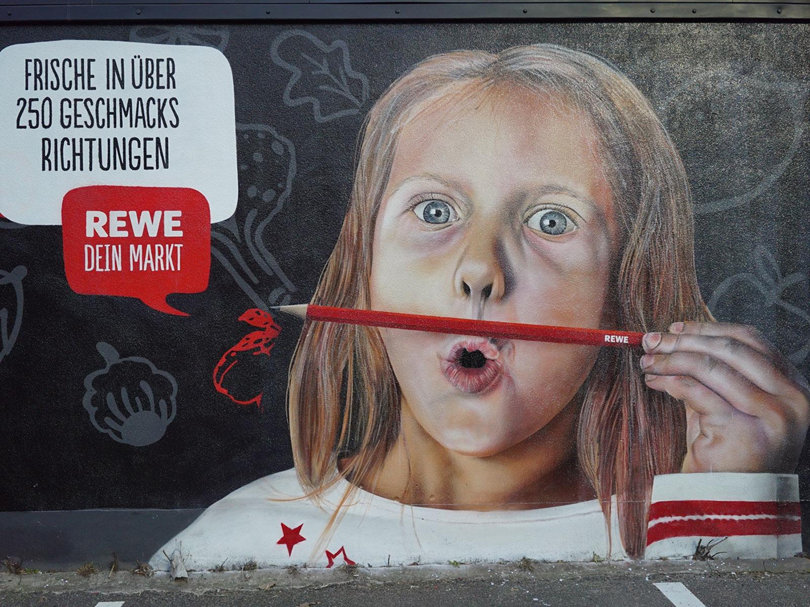 graffitiauftrag-graffitikuenstler-artmos4-rewe-skyline-obst-gesicht-schrift-wappen-aussen-schwarz-bunt-fotorealistisch-illustrativ-handel